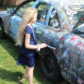 little girl painting the door of David's paint-covered car