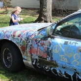 child adds paint to David's colorful car